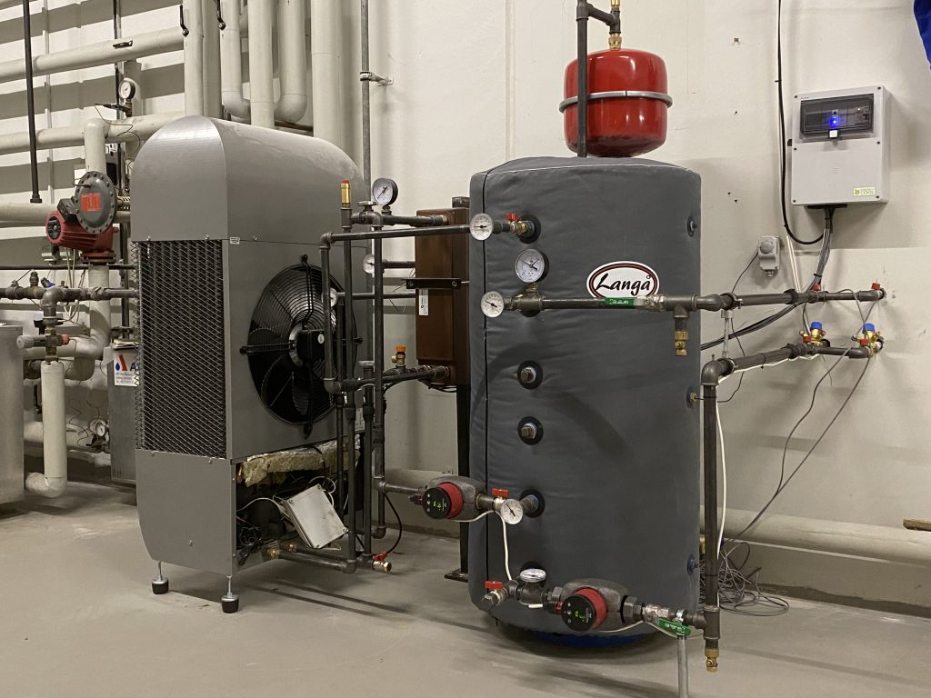 The  absorption chiller is the grey instrument at left.  The pilot chiller is a small unit of 2.5 kW. It cools the district heating water from 60 degrees to 13-18 degrees and passes it through a valve into a fan coil to cool the air.  Credit: GEV
